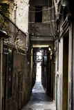 The narrow streets of the city of Genoa Italy. Old cobblestone road in the window grilles. Beautiful Perspective Lane. A good plac Royalty Free Stock Photos