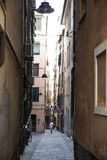 The narrow streets of the city of Genoa Italy. Old cobblestone road in the window grilles. Beautiful Perspective Lane. A good plac Stock Photos