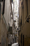 The narrow streets of the city of Genoa Italy. Old cobblestone road in the window grilles. Beautiful Perspective Lane. A good. The streets of Genoa Italy.The stock images