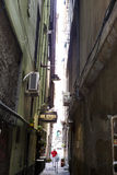 The narrow streets of the city of Genoa Italy. Old cobblestone road in the window grilles. Beautiful Perspective Lane. A good. The streets of Genoa Italy.The stock photo