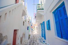 The narrow streets of greek island with blue balconies, stairs and flowers. Beautiful architecture building exterior Royalty Free Stock Photography