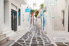 The narrow streets of greek island with cat. Beautiful architecture building exterior with cycladic style. The narrow streets of the island with blue balconies stock photo
