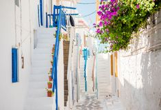 The narrow streets of the island with blue balconies, stairs and flowers. Amazing colorful stairs on beautiful narrow streets of greek island with balconies and Stock Photography