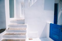 The narrow streets of the island with blue balconies, stairs and flowers in Greece. Beautiful architecture building exterior with cycladic style royalty free stock image