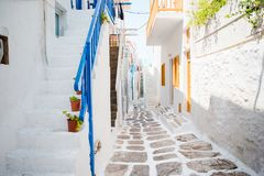 The narrow streets of the island with blue balconies, stairs and flowers. The narrow streets of greek island with blue balconies, stairs and flowers. Beautiful Stock Image