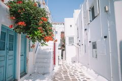 The narrow streets of the island with blue balconies, stairs and flowers. The narrow streets with blue balconies, stairs, white houses and flowers in beautiful royalty free stock image