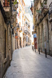 Narrow streets with medeival architecture in Alicante old town historic district Santa Cruz on the way to Santa Barbara mountain. Paved path Stock Images