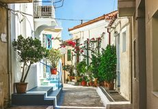 Narrow streets of Neorio town in Poros island, Greece; Old whit. E houses with flowers Stock Photography