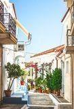 Narrow streets of Neorio town in Poros island, Greece; Old whit. E houses with flowers Royalty Free Stock Photos