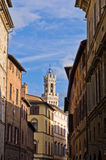 Narrow streets and old buildings in Siena, clock tower in background Royalty Free Stock Images