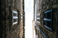 The narrow streets of the old city of Dubrovnik in Croatia, the bottom view of the sky between the stone walls of houses. History, urban, exterior, tourist stock photo