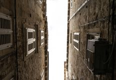 The narrow streets of the old city of Dubrovnik in Croatia, the bottom view of the sky between the stone walls of houses royalty free stock image