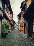 Narrow streets of the old Eguisheim with half-timbered medieval houses along the famous wine route in Alsace, France. Narrow streets of the old Eguisheim village royalty free stock photography