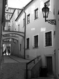 Narrow streets of Prague. Black and white photo of narrow street with delicate lantern on the wall and reflections from windows on the opposite wall, Prague Royalty Free Stock Image