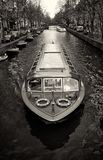 Narrow tour boat in Amsterdam Stock Photos