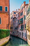 Narrow Venetian canal with emerald water. Along the canal are bright residential buildings. stock photo