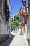 Narrow village street in Corfu, with flags and flowers Royalty Free Stock Photo