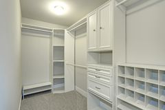 Narrow walk-in closet lined with built-in drawers. Clothes rails and shelving over brown carpet floor royalty free stock photography