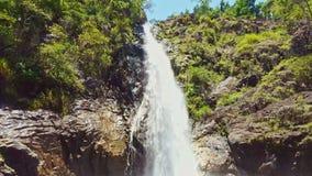 Narrow Waterfall between Rocks Falls into Pond in Tropical Park. Narrow waterfall between forestry rocks falls into pond in tropical national park stock video footage