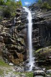 Narrow white stream of water flows over a wet stone cliff Stock Photo
