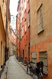 Narrow street in old town of Stockholm. Narrow wiggle street with standing bike and lamps on orange and red colour walls in old town of Stockholm Royalty Free Stock Photo