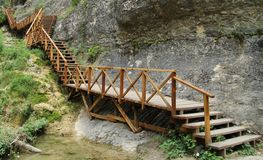 Narrow wooden path suspended over rocks Stock Image