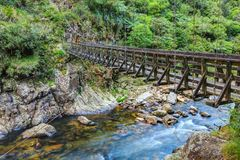 Narrow wooden suspension bridge over river in rugged terrain royalty free stock photo