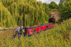 Narrowboat about to enter Tardebigge Tunnel. Holidaymakers on the Worcester and Birmingham Canal look anxiously as they position their narrowboat to enter the royalty free stock images