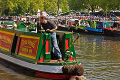 Narrowboats at Canalway Cavalcade. One of the boats taking visitors on trips, passes traditionally decorated Narrowboats moored in Little Venice for the annual Stock Image