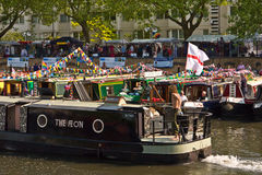 Narrowboats at Canalway Cavalcade. One of the procession of boats passes traditionally decorated Narrowboats moored in Little Venice for the annual Canalway Royalty Free Stock Photography