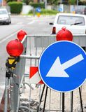 Narrowing of the roadway with red signal lamps and a road sign t Royalty Free Stock Photos
