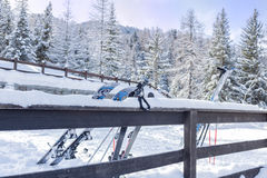 Narty i narciarscy słupy opiera przeciw ogrodzeniu zdjęcie stock