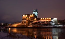 Narva castle. Night view of Herman Castle with reflection of lights on the water Royalty Free Stock Photo