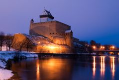 Narva castle by evening. Illuminated Narva castle and it reflection in water Royalty Free Stock Photo