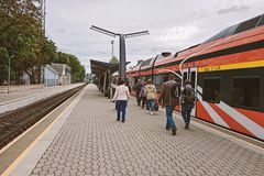 People walk along the platform to the train. NARVA, ESTONIA - SEPTEMBER 12, 2018: People walk along the platform to the train carriage at the renewed Narva royalty free stock photos