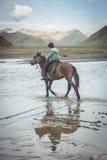 NARYN-LANDSKAP, Kirgizistan - Juli 21, 2016: Ung pojke som rider hans häst i aftonen, till andra sidan av en stark flod nära den Arkivfoto