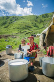 NARYN PROVINCE, KYRGYZSTAN - JULY 20 2016 Young boy and mother making butter from milk. In front of their nomadic tent on the high mountain pass between Osh royalty free stock photography