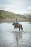 NARYN PROVINCE, KYRGYZSTAN - JULY 21 2016 Young boy riding his horse. In the evening, to the other side of a strong river near its house Stock Images