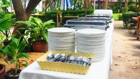 Narządzanie bufeta stół z karmowymi tacami, naczynia, łyżki i rozwidlenia dla lunchu, bawimy się obrazy royalty free