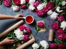 Narzędzi i akcesoriów kwiaciarni potrzeba dla robić up bukietowi z peoni: kraft papier, nożyce, sznurek, karkade herbata obraz royalty free