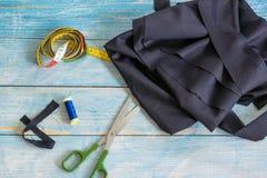 Narzędzia dla szyć: tkanina, nożyce, szpilki, taśmy miara na błękitnego drewnianego tła odgórnym widoku, mieszkanie nieatutowy zdjęcie stock