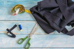 Narzędzia dla szyć: tkanina, nożyce, szpilki, taśmy miara na błękitnego drewnianego tła odgórnym widoku, mieszkanie nieatutowy fotografia royalty free