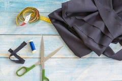 Narzędzia dla szyć: tkanina, nożyce, szpilki, taśmy miara na błękitnego drewnianego tła odgórnym widoku, mieszkanie nieatutowy fotografia stock