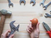 Narzędzie i jajko na drewnianym tle Pojęcie powikłani problemy wyzwanie może rozwiązujący obraz royalty free