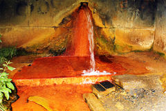 Narzan mineral water spring in Caucasus mountains, Georgia. High concentration of iron gives it rusty orange color Stock Photo