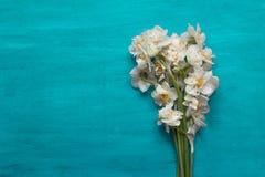 Narzissenblumenstrauß auf dem aquamarinne Hintergrund Stockfoto