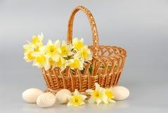 Narzissenkorb, Ostereier im Korb, Narzissenblumenfrauen des Frühlinges gelber oder Muttertag stockfotografie