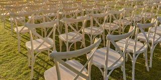 Nasłoneczneni biali krzesła na jaskrawym - zielony gazon zdjęcie stock