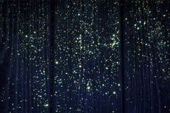 Nas estrelas amarelas e verdes de madeira azuis profundas do fulgor do fundo Natal imagem de stock