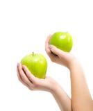 Nas mãos bonitas uma maçã dois verde, isolada no fundo branco Foto de Stock
